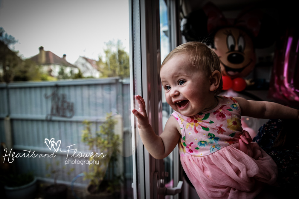 a toddler is waving out of the window when she sees her mummy outside