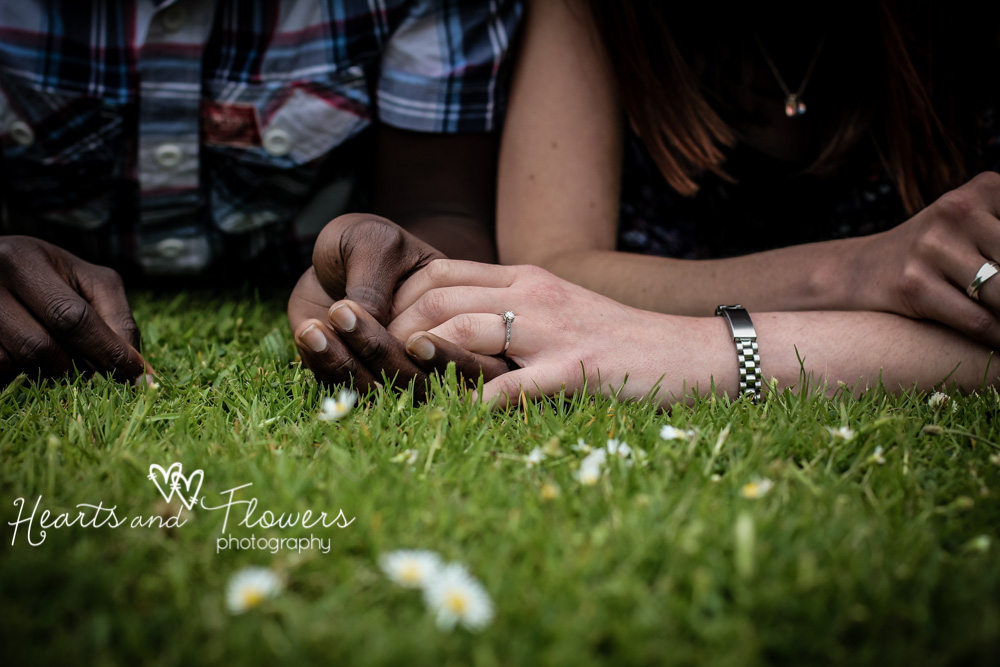 close up of a couple holding hands in the grass with some daisies