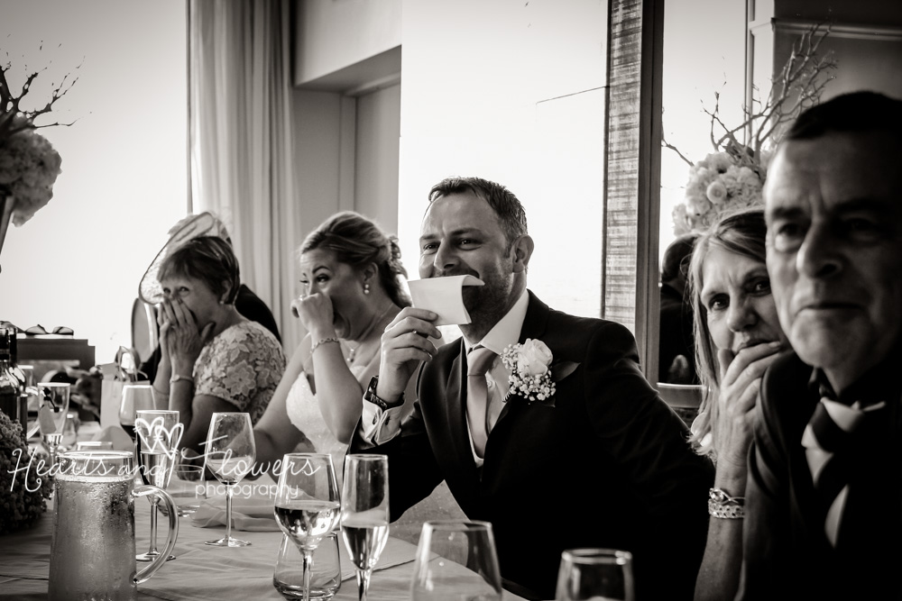 bride and groom laughing during the best mans speech