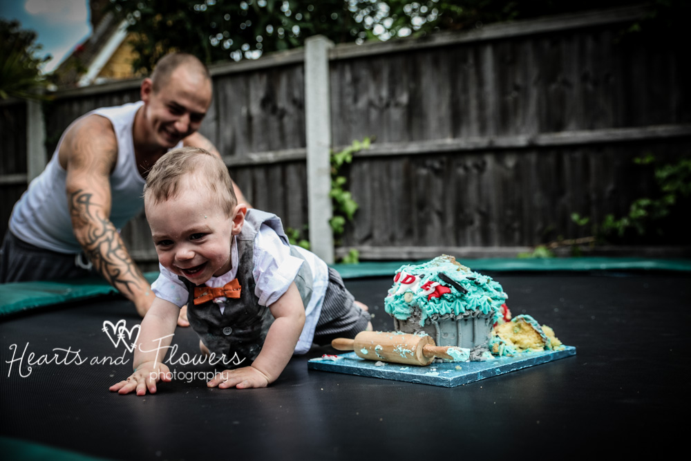 a baby boy on his trampoline with his birthday cake doing a cake smash