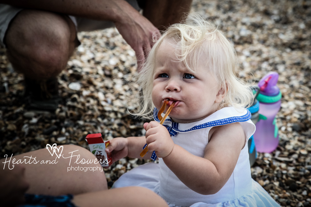 a little girl is eating chewy sweets on the beach