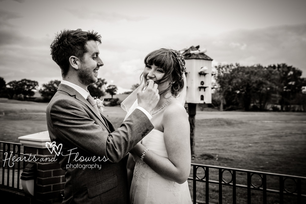 during pictures outdoors, a groom is taking hair out of his brides moth. it got blown there in the wind.