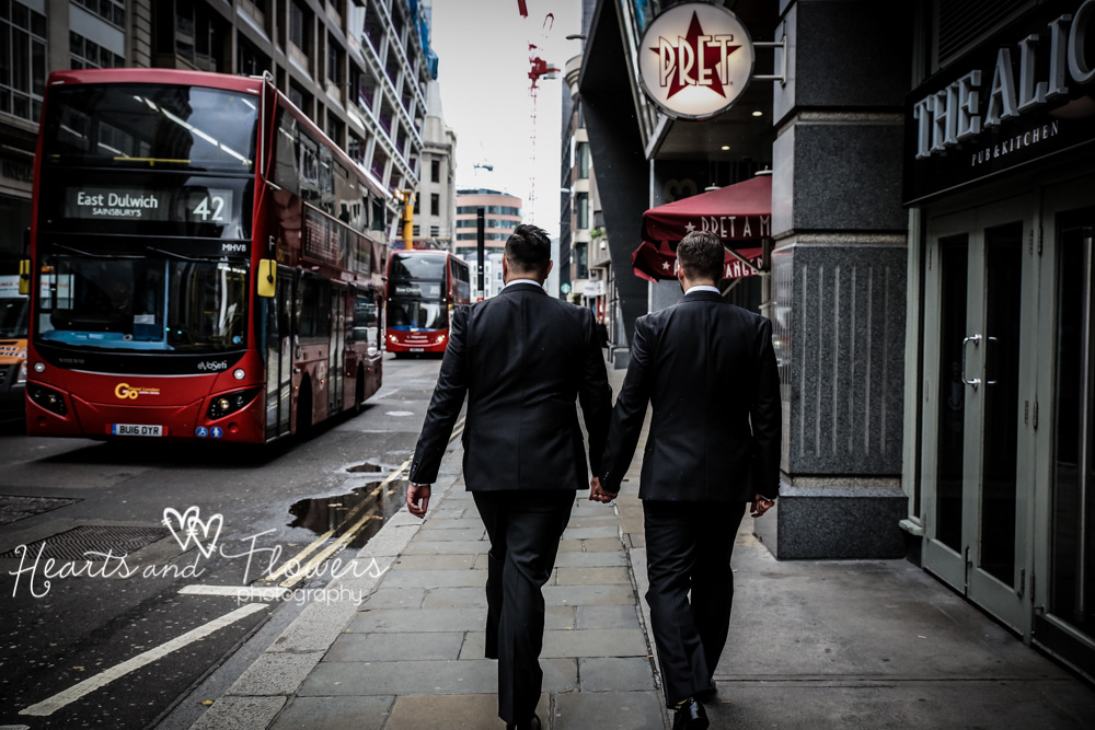 Two grooms in tuxedos walking along a london street.
