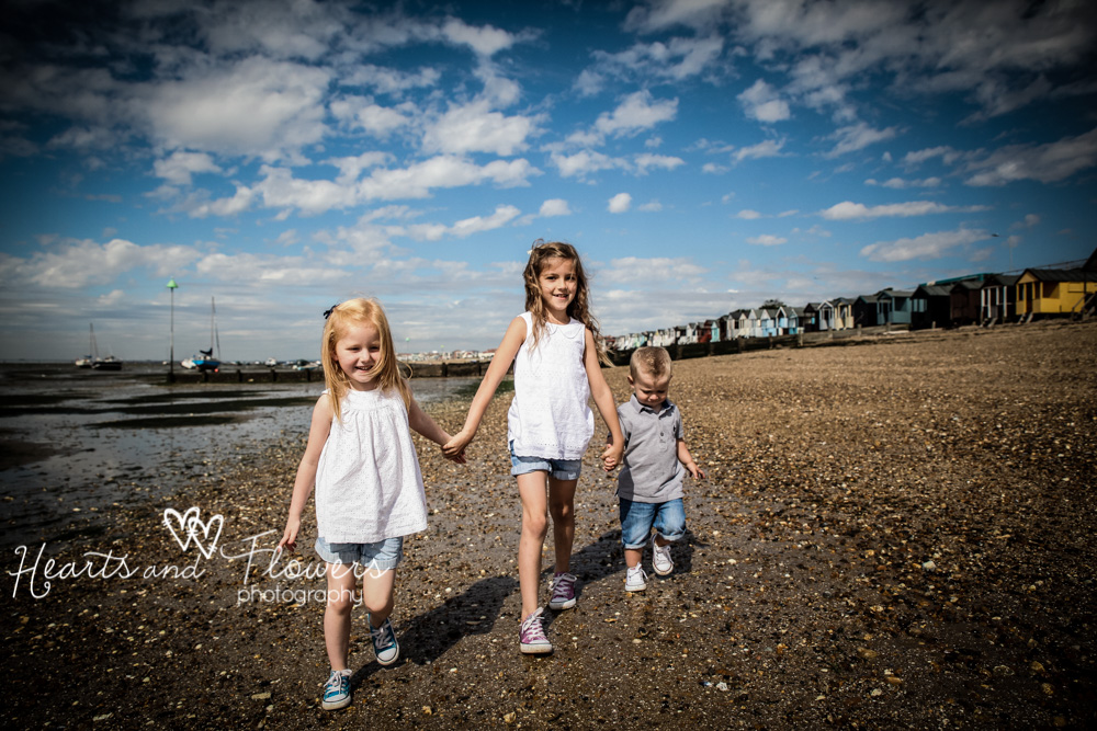 three children walk along the beach together