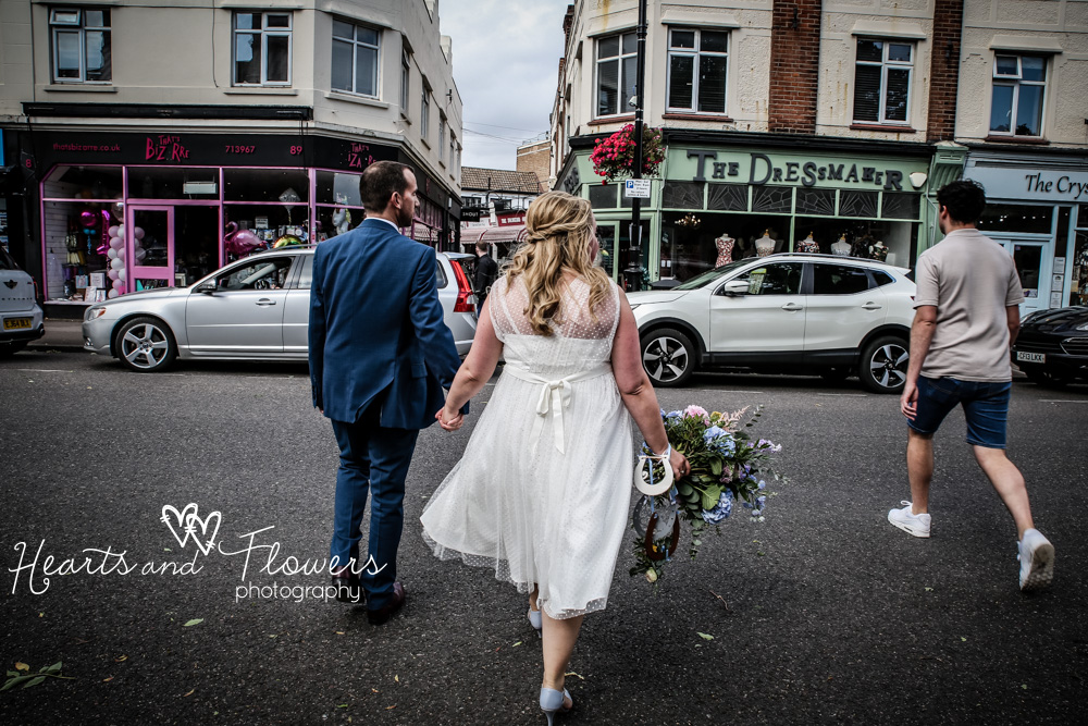 a bride and groom are crossing a street of shops